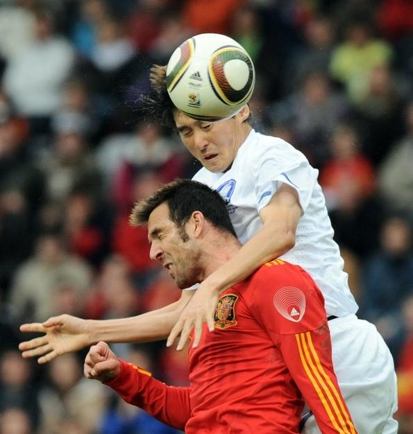 Carlos Marchena de España en busca del balón contra Lee Jung Soo