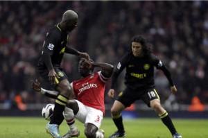 Roger Espinoza (Der) y Arouna Koné marcan a Bacary Sanga del Arsenal